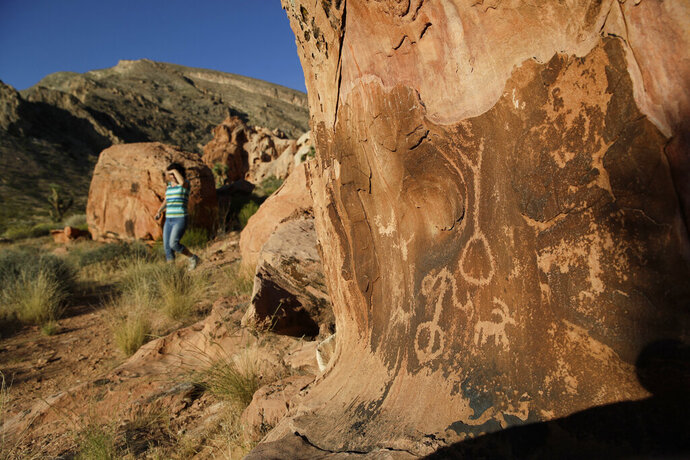FILE - In this May 26, 2017, photo, Susie Gelbart walks near petroglyphs at the Gold Butte National Monument near Bunkerville, Nev. U.S. Interior Secretary David Bernhardt says he has no plans for additional changes to Gold Butte and other national monuments as recommended by his predecessor, but says it's ultimately up to President Donald Trump. (AP Photo/John Locher, File)