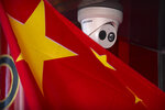 A Chinese flag hangs near a Hikvision security camera outside of a shop in Beijing, Tuesday, Oct. 8, 2019. The United States is blacklisting a group of Chinese tech companies that develop facial recognition and other artificial intelligence technology that the U.S. says is being used to repress China's Muslim minority groups. (AP Photo/Mark Schiefelbein)