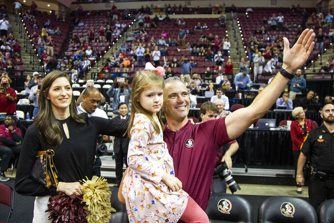 Florida State's new head football coach Mike Norvell, his wife Maria and five year old daughter Mila are introduced during a time out in the first half of an NCAA college basketball game against Clemson in Tallahassee, Fla., Sunday, Dec. 8, 2019. (AP Photo/Mark Wallheiser)