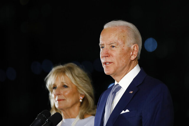 FILE - In this March 10, 2020, file photo, Democratic presidential candidate former Vice President Joe Biden, accompanied by his wife Jill, speaks to members of the press at the National Constitution Center in Philadelphia. Biden has no foreseeable plans to resume in-person campaigning amid a pandemic that is testing whether a national presidential election can be won by a candidate communicating almost entirely from home. (AP Photo/Matt Rourke)