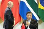 China's President Xi Jinping, right, and Russia's President Vladimir Putin attend a meeting with members of the Business Council and management of the New Development Bank during the BRICS emerging economies at the Itamaraty palace in Brasilia, Brazil, Thursday, Nov. 14, 2019. (AP Photo/Pavel Golovkin, Pool)