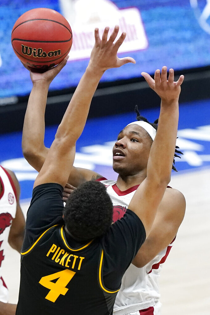 Arkansas' JD Notae shoots against Missouri's Javon Pickett (4) in the first half of an NCAA college basketball game in the Southeastern Conference Tournament Friday, March 12, 2021, in Nashville, Tenn. (AP Photo/Mark Humphrey)