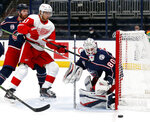 THIS CORRECTS THAT KIVLENIEKS DIED OF CHEST TRAUMA FROM AN ERRANT FIREWORKS MORTAR BLAST AND NOT A SUBSEQUENT FALL AS AUTHORITIES PREVIOUSLY REPORTED - FILE - Columbus Blue Jackets goalie Matiss Kivlenieks, right, stops a shot in front of Detroit Red Wings forward Valtteri Filppula, center, and Blue Jackets defenseman Vladislav Gavrikov during the first period of an NHL hockey game in Columbus, Ohio, in this Saturday, May 8, 2021, file photo. The Columbus Blue Jackets and Latvian Hockey Federation said Monday, July 5, 2021, that 24-year-old goaltender Matiss Kivlenieks has died. A medical examiner in Michigan says an autopsy has determined that Columbus Blue Jackets goaltender Matiss Kivlenieks died of chest trauma from an errant fireworks mortar blast, and not a fall as authorities previously reported. Police in Novi, Michigan, said the mortar-style firework tilted slightly and started to fire toward people nearby Sunday night, July 4. (AP Photo/Paul Vernon, File)