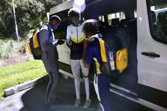 Carver College get in their van before heading back to Atlanta, Ga., after their NCAA college basketball game against Florida International Monday, Dec. 21, 2020, in Miami. (AP Photo/Gaston De Cardenas)