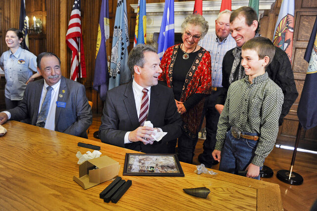 FILE - In this April 16, 2016, file photo, Montana Gov. Steve Bullock accepts a fossilized rib and tail vertebrae from a triceratops from Luke Phipps, 12, at the State Capitol in Helena, Mont., after the governor signed a bill to clarify that fossils are part of a property's surface rights, not its mineral rights, unless a contract separating the ownership says otherwise. The 9th U.S. Circuit Court of Appeals on June 17, 2020, upheld a federal judge's ruling that said dinosaur fossils are part of a property's surface estate in an ongoing battle over ownership of millions of dollars of fossils unearthed on an eastern Montana ranch. (Thom Bridge/Independent Record via AP, File)