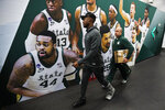 Injured Michigan State guard Joshua Langford, left, walks to the court before a practice session for the semifinals of the Final Four NCAA college basketball tournament, Friday, April 5, 2019, in Minneapolis. (AP Photo/Charlie Neibergall)