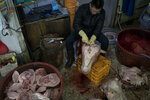 A man cleans a cow's head for sale at the traditional market in Gangneung, South Korea, Tuesday, Feb. 13, 2018. Markets like this one are a common sight in South Korea. And while the Pyeongchang promoters are hoping it will impress the foreign tourists here for the games, it hasn't been given much of an Olympic makeover.  (AP Photo/Felipe Dana)