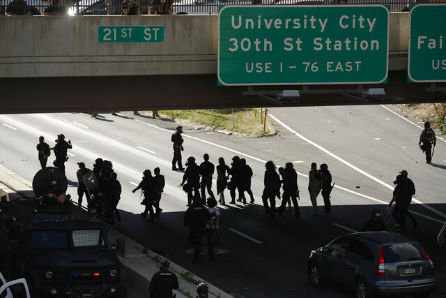 FILE—In this file photo from June 1, 2020, protesters march down Interstate 676 in Philadelphia, during a march calling for justice over the death of George Floyd.  The Philadelphia district attorney has announced Wednesday, July 22, charges against a police officer seen on video lowering the masks of protesters to douse them with pepper spray as they knelt on the highway during a protest on June 1.  (AP Photo/Matt Rourke, File)