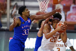 Texas forward Jericho Sims (20) fights for a rebound with Kansas forward David McCormack (33) during the second half of an NCAA college basketball game, Tuesday, Feb. 23, 2021, in Austin, Texas. (AP Photo/Eric Gay)
