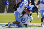 Duke quarterback Chase Brice (8) is tackled by North Carolina linebacker Chazz Surratt (21)  during the first half of an NCAA college football game at Wallace Wade Stadium, Saturday, Nov. 7, 2020, in Durham, N.C. (Jim Dedmon/Pool Photo via AP)