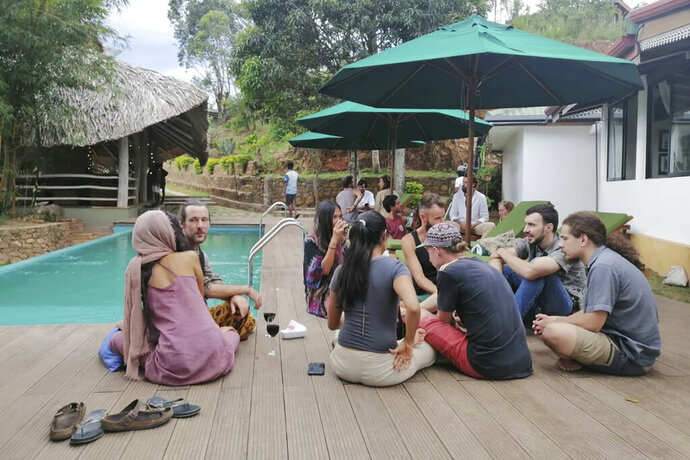 """In this April, 2020, photo, stranded tourists rest at the Cafe Chill in Ella, a tourist hot spot about 200 kilometers (120 miles) east of the capital Colombo, Sri Lanka. When flights were canceled and airports shut down, cafe owner Darshana Ratnayake decided to organize free food and shelter for several dozen stranded tourists. """"We were totally blown away,"""" one of the tourists, 31-year-old cruise line entertainment director Alex Degmetich, said of the gesture. 40 tourists were stranded in Ella after the Sri Lankan government imposed a nationwide curfew on March 20 to curb the spread of the virus, sealing off entire regions of the Indian Ocean island nation. (Cafe Chill via AP)"""