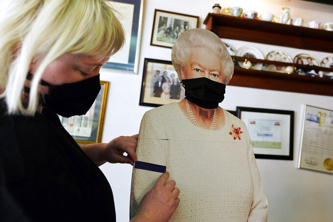 Molly Carew, manager of Tea & Sympathy, a British restaurant and shop, places a black arm band on a cardboard cutout of Queen Elizabeth II, to mourn the death of Britain's Prince Philip in New York, Friday, April 9, 2021.  (AP Photo/Richard Drew)