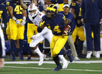 Michigan defensive back Josh Metellus (14) returns an interception intended for Wisconsin wide receiver Kendric Pryor (3) during the first half of an NCAA college football game in Ann Arbor, Mich., Saturday, Oct. 13, 2018. (AP Photo/Paul Sancya)