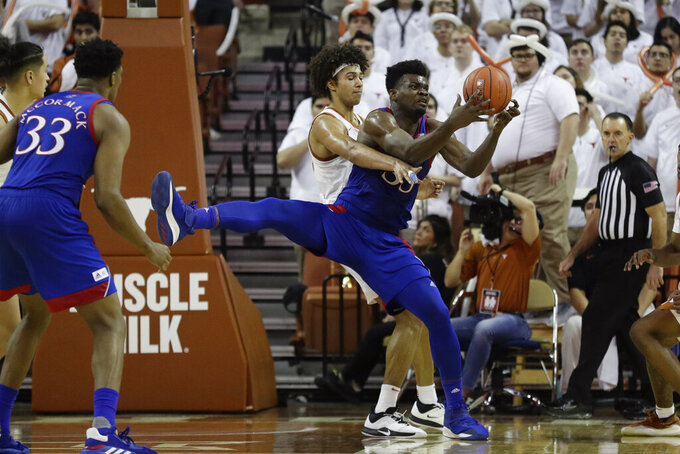Kansas center Udoka Azubuike (35) is pressured by Texas forward Jericho Sims (20) as he grabs a rebound during the second half of an NCAA college basketball game, Saturday, Jan. 18, 2020, in Austin, Texas. (AP Photo/Eric Gay)