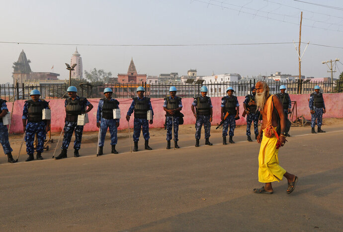 A Sadhu, Hindu holy man, walks past security officers standing guard in Ayodhya, India , Saturday, Nov. 9, 2019. India's security forces were on high alert ahead of the Supreme Court's verdict Saturday in a decades-old land title dispute between Muslims and Hindus over plans to build a Hindu temple on a site where Hindu hard-liners demolished a 16th century mosque in 1992, sparking deadly religious riots. (AP Photo/Rajesh Kumar Singh)
