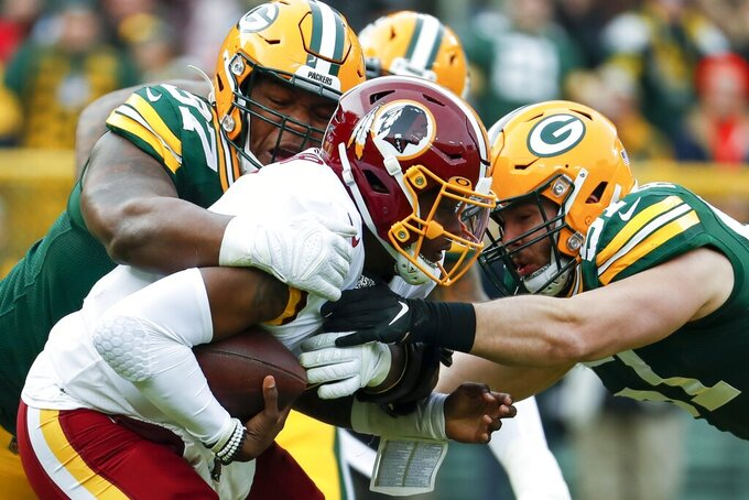 Washington Redskins' Dwayne Haskins is sacked by Green Bay Packers' Kenny Clark and Kyler Fackrell during the first half of an NFL football game Sunday, Dec. 8, 2019, in Green Bay, Wis. (AP Photo/Matt Ludtke)