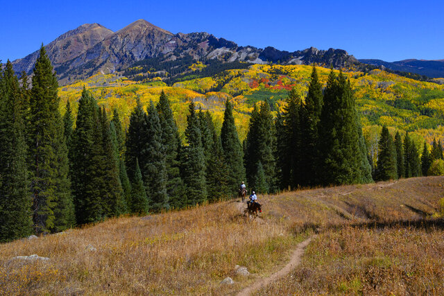 In this Oct. 6, 2019 photo, a pair of horseback riders make their way toward Beckwith Pass on the Cliff Creek Trail near Crested Butte, Gunnison, County, Colo. Records reviewed by The Associated Press show that an exclusive group of Texans stood to benefit when the state's attorney general, Ken Paxton, urged the small Colorado county to reverse a public health order during the coronavirus outbreak. Paxton this month told Gunnison County that banning Texans from their property in Colorado during the outbreak was unconstitutional. (Christian Murdock/The Gazette via AP)