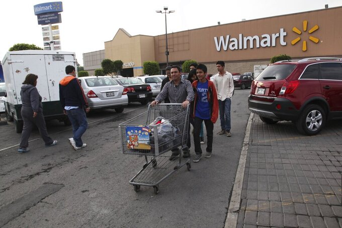 FILE - In this Dec. 26, 2013 file photo, a family leaves a local Walmart in Mexico City. Walmart de Mexico, the country's biggest retailer, announced the week of June 18, 2021, that its grocery store baggers wouldn't be allowed back, as the coronavirus pandemic and changing consumer habits threaten to put an end to a decades-old practice of allowing elderly people in Mexico to earn extra income as baggers. (AP Photo/Marco Ugarte, File)
