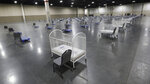 Cots and cribs are shown at the Mountain America Expo Center Monday, April 6, 2020, in Sandy, Utah. The State of Utah has contracted with Salt Lake County to use the Mountain America Expo Center as an alternate care site, or hospital overflow. This is not a site for COVID-19 patients. It is simply an overflow site for certain types of care, should the need arise. It will initially be stocked with 250 beds and medical equipment. (AP Photo/Rick Bowmer)
