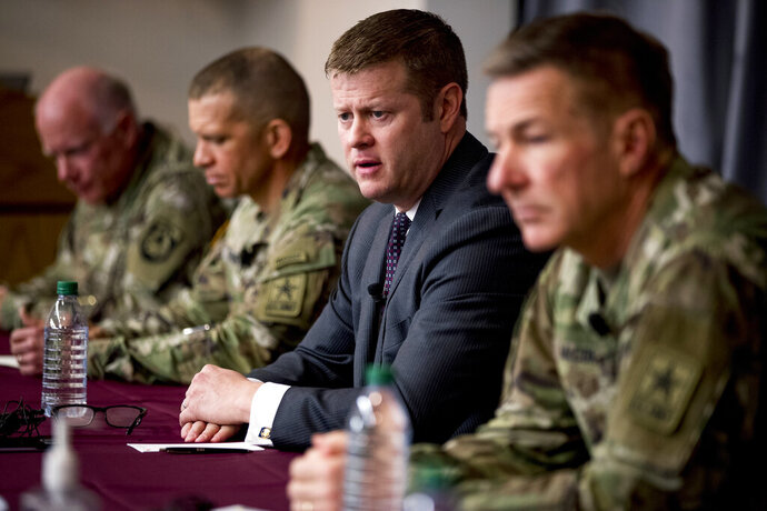 FILE - In this March 19, 2020, file photo Secretary of the Army Ryan McCarthy, center, accompanied by Col. Darrin Cox, left, Sgt. Maj. Michael Grinston, second from left, and Gen. James McConville, Chief of Staff of the Army, speaks at a news conference at U.S. Army Medical Research and Development Command at Fort Detrick in Frederick, Md. McCarthy announced Thursday, June 25, that beginning in August the service will no longer include soldiers' photos when they are being considered for promotion. He and McConville, said however, that they are still reviewing whether to redact the box on the form that identifies a person's race when soldiers are up for promotion. (AP Photo/Andrew Harnik, File)