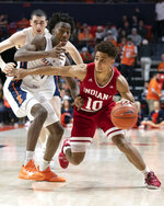 FILE - In this March 7, 2019, file photo, Indiana guard Rob Phinisee (10) drives to the basket against Illinois guard Ayo Dosunmu (11) during the second half of an NCAA college basketball game in Champaign, Ill. Phinisee understands the secret to being an effective point guard. He must find the proper balance between aggressive scorer and creative distributor while using his vision to help Indiana's offense operate efficiently.(AP Photo/Stephen Haas, File)