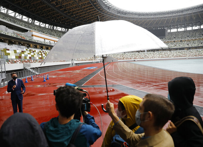 World Athletics President Sebastian Coe, top left, wearing a protective face mask speaks to media as he inspects at the National Stadium, the main stadium of Tokyo 2020 Olympics and Paralympics, in Tokyo Thursday, Oct. 8, 2020. (Issei Kato/Pool Photo via AP)