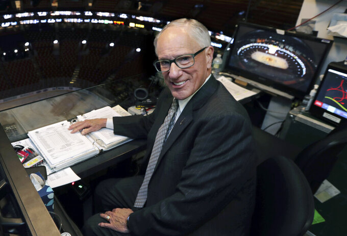 FILE - In this Wednesday, May 29, 2019, file photo, NBC hockey broadcaster Mike Emrick poses for a photo while preparing to call Game 2 of the NHL hockey Stanley Cup Final between the St. Louis Blues and the Boston Bruins, in Boston. Hall of Fame hockey broadcaster Mike Emrick is retiring after a career of almost 50 years behind the microphone, including the past 15 as the voice of the NHL in the United States. (AP Photo/Charles Krupa, File)