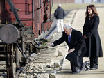 United States Vice President Mike Pence kneels beside his wife Karen, right, at a historic freight car during their visit to the former Nazi concentration camp Auschwitz-Birkenau in Oswiecim, Poland, Friday, Feb. 15, 2019. The freight car was used to transport Jews to the death camp. (AP Photo/Michael Sohn)