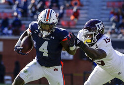 Auburn running back Tank Bigsby (4) tries to get around Texas A&M defensive lineman Jeremiah Martin (15) as he caries the ball during the second half of an NCAA college football game on Saturday, Dec. 5, 2020, in Auburn, Ala. Texas A&M won 28-20. (AP Photo/Butch Dill)