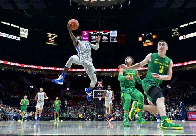 Memphis guard Damion Baugh, left, shoots next to Oregon guard Payton Pritchard during the first half of an NCAA college basketball game in Portland, Ore., Tuesday, Nov. 12, 2019. (AP Photo/Craig Mitchelldyer)