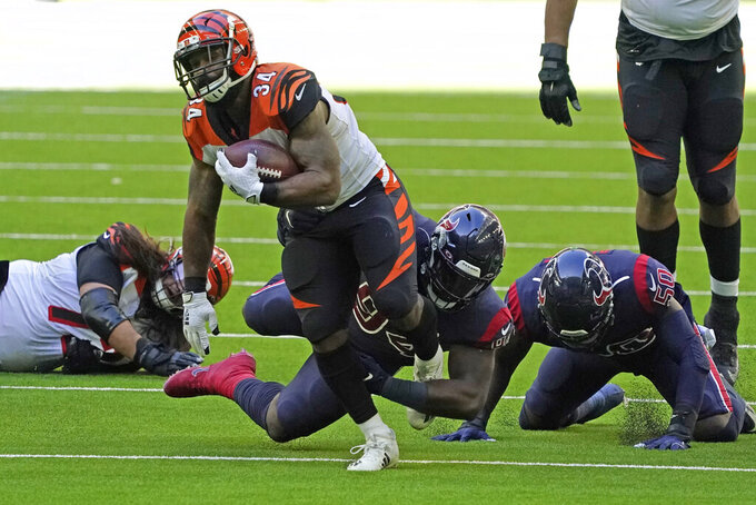 Cincinnati Bengals running back Samaje Perine (34) breaks away from Houston Texans defensive end Charles Omenihu (94) to run for a 46-yard touchdown during the second half of an NFL football game Sunday, Dec. 27, 2020, in Houston. (AP Photo/Sam Craft)