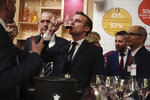 French President Emmanuel Macron drinks wine during a visit to the International Agriculture Fair (Salon de l'Agriculture) at the Porte de Versailles exhibition center in Paris, Saturday, Feb. 22, 2020. (Christophe Petit Tesson/Pool via AP)