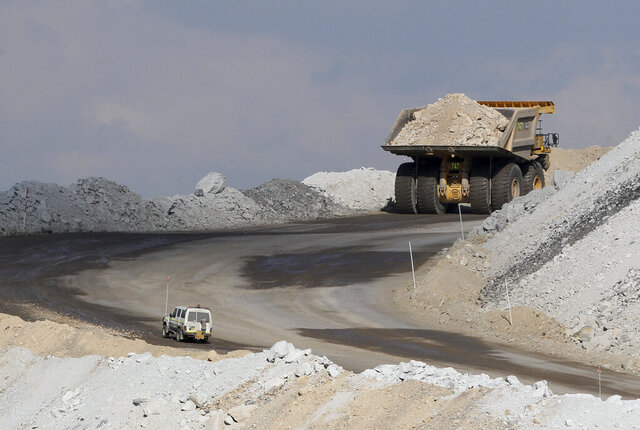 In this Sept. 11, 2012, file photo, a four-wheel-drive vehicle follows a large mining truck as it makes its way to the top of a Boggabri coal mine near Gunnedah, Australia, 450 kilometers (280 miles) northwest of Sydney. Australia's prime minister said Tuesday, Dec. 15, 2020, that China would be in breach of World Trade Organization rules as well as a bilateral free trade agreement if it banned Australian coal. (AP Photo/Rob Griffith, File)