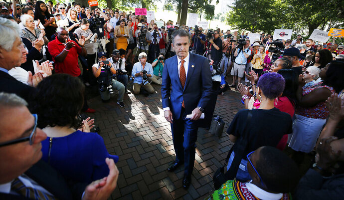 Gov. Ralph Northam walks away from the lectern after speaking at a rally against gun violence held on the Virginia State Capitol grounds, in Richmond, Va., Tuesday, July 9, 2019. Gov. Northam has called the legislature into special session to deal with the issues after 13 people were gunned down in a Virginia Beach mass shooting in May. (Joe Mahoney/Richmond Times-Dispatch via AP)
