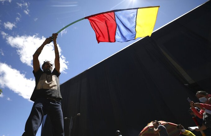A man waves a banner representing Colombia's national colors during an anti-government protest triggered by proposed tax increases on public services, fuel, wages and pensions in Bogota, Colombia, Wednesday, June 2, 2021. (AP Photo/Fernando Vergara)