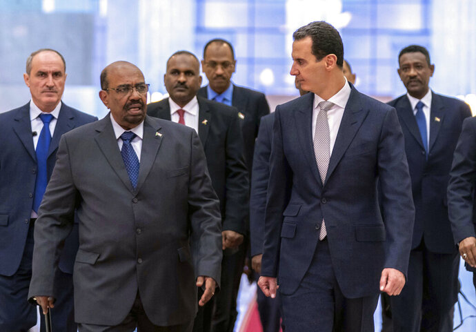 FILE - In this file photo released by the Syrian official news agency SANA Dec. 16, 2018, Syrian President Bashar Assad, right, meets with Sudan's President Omar Bashir in Damascus, Syria.  Assad has survived years of war and millions of dollars in money and weapons aimed at toppling him. Now after nearly eight years of conflict, he is poised to be readmitted to the fold of Arab nations, a feat once deemed unthinkable as he brutally crushed a years-long uprising against his family's rule.  (SANA via AP, File)