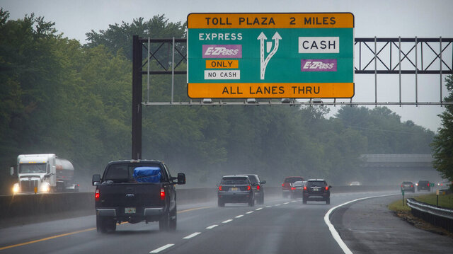 FILE - This photo from Friday July 31, 2020, shows toll signage as motorists travel along the New Jersey Turnpike in Carneys Point, N.J. The first part of a one-two punch for New Jersey drivers takes effect Sunday with hikes on the state's two major toll roads. The state turnpike authority approved the increases in May over objections of residents who criticized the timing during the pandemic. (AP Photo/Matt Slocum, File)
