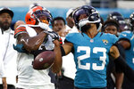 Cleveland Browns wide receiver Donovan Peoples-Jones, left, drops a pass as he is defended by Jacksonville Jaguars cornerback C.J. Henderson (23) during the first half of an NFL preseason football game, Saturday, Aug. 14, 2021, in Jacksonville, Fla. (AP Photo/Stephen B. Morton)