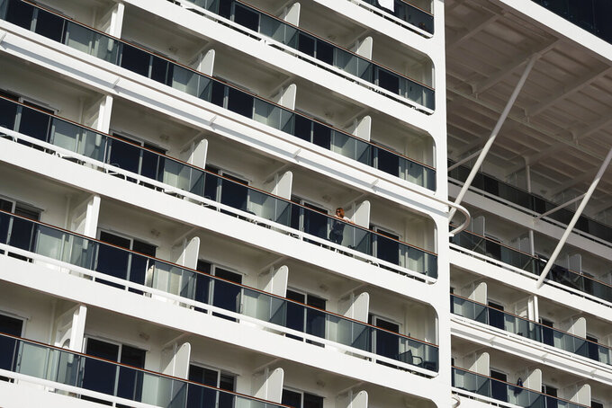 A passenger stand on the terrace of a cabin of the MSC Grandiosa cruise ship in Civitavecchia, near Rome, Wednesday, March 31, 2021. MSC Grandiosa, the world's only cruise ship to be operating at the moment, left from Genoa on March 30 and stopped in Civitavecchia near Rome to pick up more passengers and then sail toward Naples, Cagliari, and Malta to be back in Genoa on April 6. For most of the winter, the MSC Grandiosa has been a lonely flag-bearer of the global cruise industry stalled by the pandemic, plying the Mediterranean Sea with seven-night cruises along Italy's western coast, its major islands and a stop in Malta. (AP Photo/Andrew Medichini)