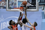 Syracuse forwards Quincy Guerrier (1) and Marek Dolezaj, right, defend while North Carolina forward Day'Ron Sharpe drives to the basket during the second half of an NCAA college basketball game in Chapel Hill, N.C., Tuesday, Jan. 12, 2021. (AP Photo/Gerry Broome)