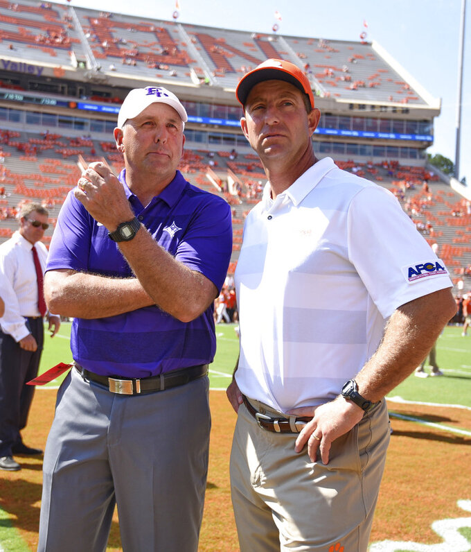 Clemson head coach Dabo Swinney, right, talks with Furman head coach Clay Hendrix before the start of an NCAA college football game Saturday, Sept. 1, 2018, in Clemson, S.C. (AP Photo/Richard Shiro)