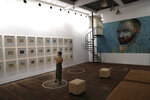A visitor looks at art pieces by Indonesian artist Hanafi as she stands on a physical distancing marker placed on the floor as a precaution against the new coronavirus during an exhibition at Kertas Gallery in di Depok, West Java, Indonesia, Thursday, July 9, 2020. (AP Photo/Tatan Syuflana)