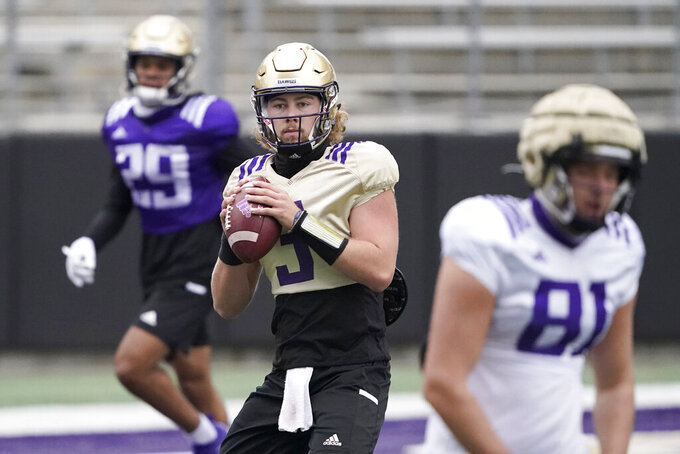 Washington quarterback Jacob Sirmon, center, drops to pass during NCAA college football practice, Friday, Oct. 16, 2020, in Seattle. (AP Photo/Ted S. Warren)
