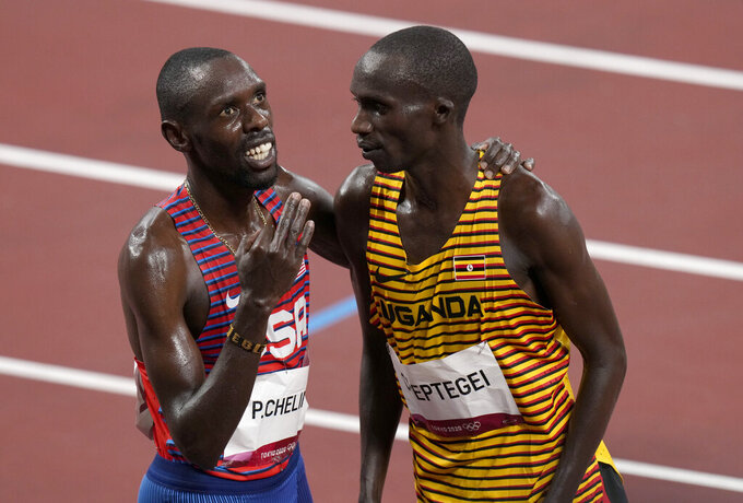 Joshua Cheptegei, of Uganda celebrates with Paul Chelimo, of United States, bronze, after winning the gold medal in the final of the men's 5,000-meters at the 2020 Summer Olympics, Friday, Aug. 6, 2021, in Tokyo, Japan. (AP Photo/Francisco Seco)