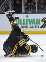 Boston Bruins defenseman Charlie McAvoy (73) is upended as he tries to control the puck during the second period of an NHL hockey game against the Pittsburgh Penguins in Boston, Monday, Nov. 4, 2019. (AP Photo/Charles Krupa)