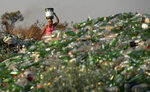 A woman carries a container of water on her head past material for recycling in the Vosloorus Township near Johannesburg, South Africa, Tuesday, Oct. 27, 2020. More than 2 million jobs have been lost during the economic downturn caused by the pandemic in South Africa, a country of 60 million people.(AP Photo/Themba Hadebe)