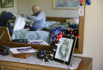 Don Long gets dressed at his home Friday, Dec. 7, 2018, in Napa, Calif., before driving to attend a number of Pearl Harbor remembrances. At right on his dresser is a photograph of him as a pilot in 1943. Retired U.S. Navy Cmdr. Don Long wasn't at Pearl Harbor when Japanese war planes started bombing Hawaii on December 7, 1941, he was on the opposite side of Oahu standing watch aboard an anchored military seaplane in Kaneohe Bay. But the wave of bombs and bullets reached his military installation soon after Pearl Harbor was struck, and the young sailor watched from afar as buildings and planes started to explode all around him. On the 77th anniversary of the attack, Long will remember from his home where the 97-year-old survivor will reflect and honor those who died. (AP Photo/Eric Risberg)