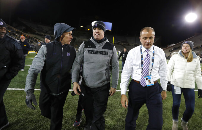 Northwestern head coach Pat Fitzgerald,, center, walks off the field after an NCAA college football game against Iowa, Saturday, Nov. 10, 2018, in Iowa City, Iowa. Northwestern won 14-10. (AP Photo/Charlie Neibergall)