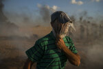A Palestinian protester wears a plastic bag on his head as a protection from tear gas fired by Israeli troops during a protest at Gaza Strip's border with Israel, east of Gaza City, Friday, Sept. 7, 2018. A teenager was killed and dozens of other Palestinians injured by Israeli fire at a border protest, Gaza officials said. (AP Photo/Felipe Dana)