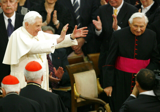 FILE - In this Saturday, Oct. 27, 2007 file photo, Pope Benedict XVI, center left, applauds, as his brother, Georg, right, looks on, during a concert by the German Symphonic Orchestra Bayerischer Rundfunk and the Bamberger Symphoniker, at the Paul VI Hall at the Vatican. The Rev. Georg Ratzinger, the older brother of Emeritus Pope Benedict XVI, who earned renown in his own right as a director of an acclaimed German boys' choir, has died at age 96. The Regensburg diocese in Bavaria, where Ratzinger lived, said in a statement on his website that he died on Wednesday, July 1, 2020. (AP Photo/Andrew Medichini, File)